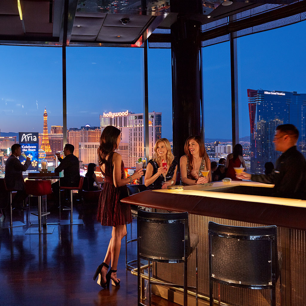 People socializing with cocktails at Skybar